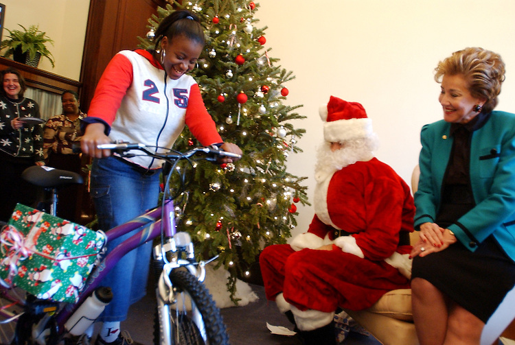 Latoya Jefferson, 10, checks out her new bike she received from Santa and the staff of Sen. Elizabeth Dole, R-N.C., right.  The staff gave presents to kids from a church group from the neigborhood of Shaw, United House of Prayer for All People, as an act of kindness toward a local Washington area.