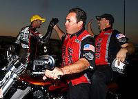 Nov 10, 2013; Pomona, CA, USA; Matt Hines (center) congratulates NHRA pro stock motorcycle rider Eddie Krawiec and crew after winning the Auto Club Finals at Auto Club Raceway at Pomona. Mandatory Credit: Mark J. Rebilas-