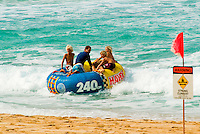 People ride the surf on an inflatable raft near a red warning flag on the north shore of Oahu.