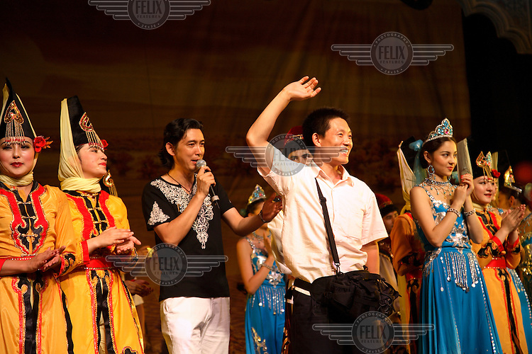 Tourists pose for pictures with performers at the end of an ethnic song and dance extravaganza at an all-you-can-eat restaurant in Urumqi.