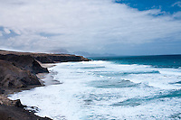 Rough seas at the beach in La Pared (Playa de La Pared), Fuerteventura, Canary Islands, Spain. <br /> The shoreline of Fuerteventura can display beautiful golden beaches intermingled with cliffs touching the sea.