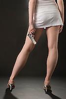 Lower body of Caucasian blonde woman facing away from camera holding handgun on black seamless
