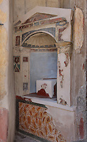 Decorated lararium niche, a shrine dedicated to the guardian spirits of the household, in the Casa dell Efebo, or House of the Ephebus, Pompeii, Italy. This is a large, sumptuously decorated house probably owned by a rich family, and named after the statue of the Ephebus found here. Pompeii is a Roman town which was destroyed and buried under 4-6 m of volcanic ash in the eruption of Mount Vesuvius in 79 AD. Buildings and artefacts were preserved in the ash and have been excavated and restored. Pompeii is listed as a UNESCO World Heritage Site. Picture by Manuel Cohen