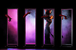 Expressive stage performance Dancing young couple in purple clouds of smoke reflecting in mirrors with eerie hands touching them from behind Conceptual artistic image from Show-ballet troup A-6 play Passion is Stronger Than Love in Kiev Ukraine April 2007 Black background Some parts of the image are blurred from motion