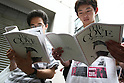 July 3, 2010 - Tokyo, Japan - People read pamphlets of the Oscar-winning dolphin hunting documentary 'The Cove' near a cinema running the movie in Tokyo, Japan, on July 3, 2010. Despite pressure from groups who say the film is anti-Japanese, 'The Cove' will be shown at six theaters in Tokyo and five other Japanese cities beginning Saturday, followed by Nagoya Cinematheque and 15 other theaters across Japan from Aug. 14.