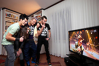 Switzerland. Canton Ticino. Losone. The brothers Ivan and Gabriel Broggini of the band Sinplus will represent Switzerland with their song Unbreakable at the Eurovision Song Contest 2012 in Baku. They are watching at home the news on the swiss italian television and celebrate their joy with some friends. Left to right: Gabriel Broggini, Lisa Panigada who was playing the bass during the concert, Christian Calzascia who takes care of the haircut of both brothers, Ivan Broggini. Gabriel Broggini is the singer and his brother Ivan plays the guitar. 11.12.2011 © 2011 Didier Ruef
