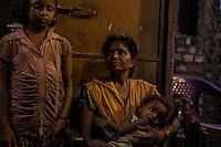 """Sonamoni Hembrom, 32 year old, photographed with her 2 children, lives in the slum of Balaram, in Jamshedpur. In 1995, her mother was accused of witchcraft and her father killed by some fellow villagers, who feared he might report to the police the accusations against the wife. The family had to leave the village of Chimihatu and all its properties behind. Two of her brothers were able to go back to their house only one month ago. """"Every night I feel so anxious that something might happen to them"""", she says."""