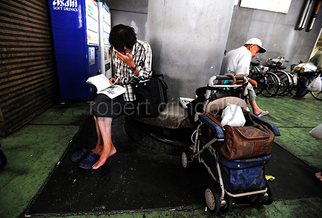 Unemployed men seeking day labor jobs kill time at a social welfare center in  the Kamagasaki district of Osaka, Japan.