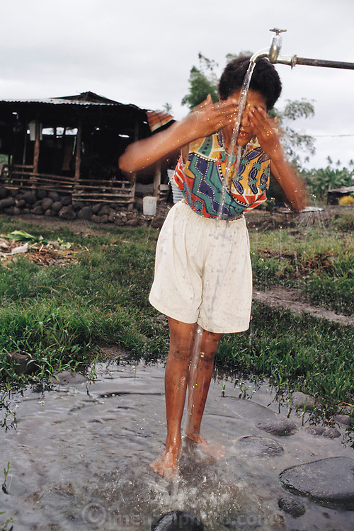 Fuao Lagavale, 13, washes her face at the water spigot outside the family's detached cooking house. The Lagavale family lives in a 720-square-foot tin-roofed open-air house with a detached cookhouse in Poutasi Village, Western Samoa. The Lagavales have pigs, chickens, a few calves, fruit trees and a vegetable garden. Material World Project.