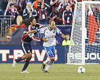 Montreal Impact midfielder Justin Mapp (21) works to clear ball as New England Revolution substitute midfielder Juan Carlos Toja (7) closes. In a Major League Soccer (MLS) match, Montreal Impact (white/blue) defeated the New England Revolution (dark blue), 4-2, at Gillette Stadium on September 8, 2013.