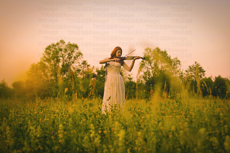 Female youth outdoors in spring wearing a white gown and playing a violin
