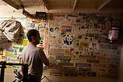Neil Brewster, radio operator, from Australia, examines a wall of various campaign stickers from Greenpeace's history, on a wall on the Greenpeace ship 'Rainbow Warrior', in transit heading towards Fukushima, Japan on Friday April 22nd 2011.