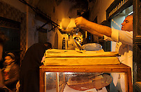 Baker weighing out Moroccan pancakes at his shop in the medina or old town of Tetouan, on the slopes of Jbel Dersa in the Rif Mountains of Northern Morocco. Tetouan was of particular importance in the Islamic period from the 8th century, when it served as the main point of contact between Morocco and Andalusia. After the Reconquest, the town was rebuilt by Andalusian refugees who had been expelled by the Spanish. The medina of Tetouan dates to the 16th century and was declared a UNESCO World Heritage Site in 1997. Picture by Manuel Cohen