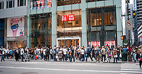 Customers outside the grand opening of the Uniqlo Flagship store on Fifth Avenue in New York on Friday, October 14, 2011.  The store is a staggering 89,000 square feet on multiple levels and is Fast Retailing's second store in the United States with a third opening next week in the Herald Square shopping district. The largest store on Fifth Avenue filled to the brim with affordable clothing it competes with stalwarts such as the Gap and Zara which are in the immediate proximity. Fast Retailing plans on opening 200 to 300 stores worldwide until 2020 and currently has 1000 stores. (© Richard B. Levine)