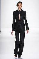 Model walks runway an EBONY LORO PIANA CASHMERE+SILK BLAZER.W/ ATTACHED UPTURNED PEAK LAPEL + DESERT HAND TOP HAND STITCHING EBONY LORO PIANA CASHMERE + SILK LEAN TROUSERS by Zang Toi, for the Zang Toi Spring 2012 My Dream Of North Africa Collection, during Mercedes-Benz Fashion Week Spring 2012.