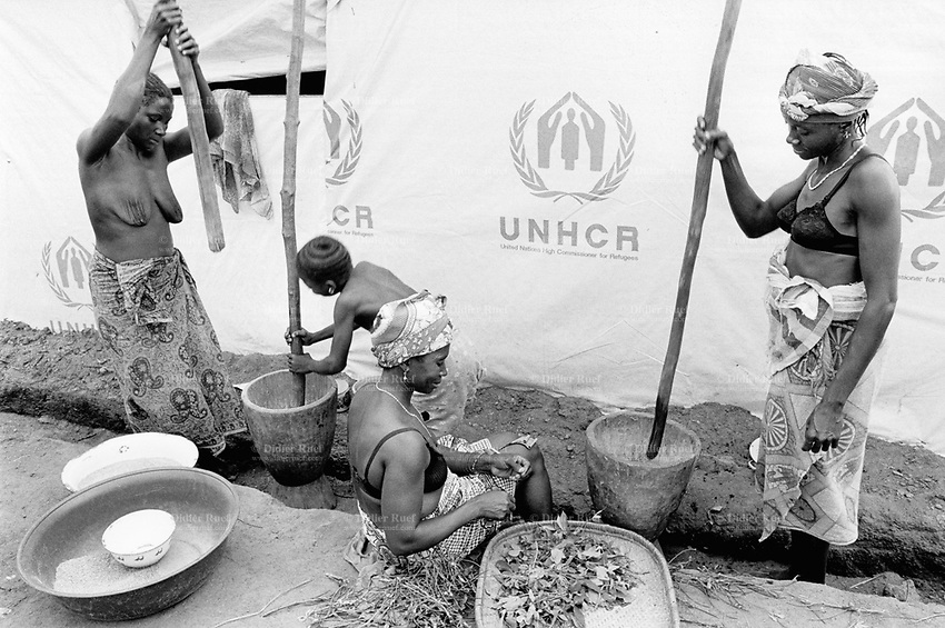 """Guinea. State of """"Guinée Forestière"""". Katkama. Women grind cereals to prepare the daily meal. UNHCR (United Nations High Commision for the refugees) transit camp for Sierra Leoneans  refugees. UNHCR's decision is to carry out the refugee evacuation movement out of the troubled camps of the """"Parrot's beak"""" region for a relocation in safer camps. Daily life outside a tent where up to 20 families with families and children share the same tent and space.   © 2001 Didier Ruef"""