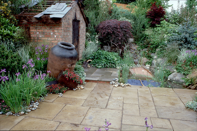 Huge Med-style urn in courtyard of pretty stone patio paving, rustic brick shed, nice landscaping irises in spring. Design by Geoff Whiten.