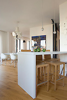 A breakfast bar visually divides the kitchen from the dining area in this loft apartment