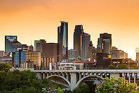 Minneapolis skyline and Tenth Avenue bridge with orange storm light.