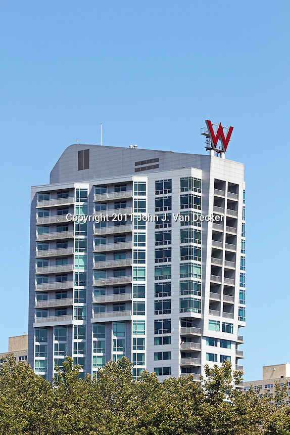 the w hotel rising above the treetops of a waterfront park. Black Bedroom Furniture Sets. Home Design Ideas