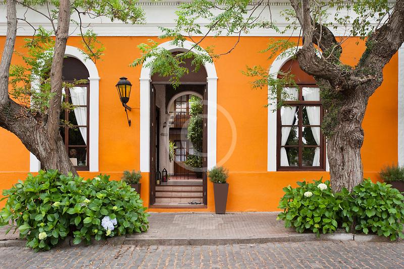 Uruguay, Colonia de Sacramento, Trees and orange facade of historic building in old town
