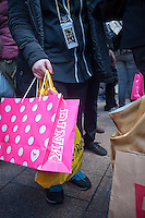 "A shopper with their Pink shopping bag in Herald Square in New York on the day after Thanksgiving, Black Friday, November 28, 2014. Many retailers, including Macy's, opened their doors on Thanksgiving evening extending the shopping day and giving Thanksgiving the nickname ""Gray Thursday"". (© Richard B. Levine)"