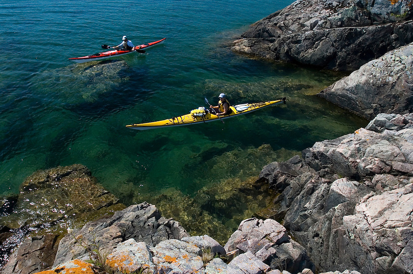 A pair of sea kayakers explore Granite Point on Lake Superior between Big Bay and Marquette Michigan.
