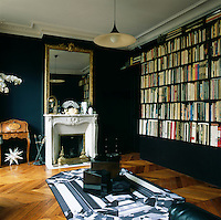 Graphic patterns, added to a simple palette of black and white create an elegant combination, whilst the contemporary furniture contrasts with the original period features in this Paris apartment. The study with its built-in bookshelves