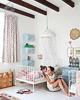 The girls' room is furnished with white-painted wrought iron beds and has some useful storage ideas