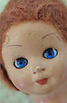 Close up of 1960s doll head with piercing blue eyes and frizzy red hair