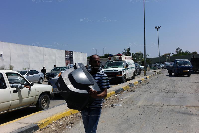 Tripoli, Libya, August 24, 2011.A man exits Khaddafi Bab Azizyah complex carrying a large TV set..