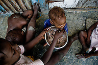 A girl feeds his younger brother by rice in the slum of Cité Soleil, Port-au-Prince, Haiti, 22 July 2008. Rice is a basic source of nutrition for all Haitians. Rice is almost entirely imported from the US. Haitian farmers can not compete with the low dumping price of the US state-aided rice. The overall situation on Haiti gets worse every year and the extreme, hardly imaginable poverty hits more and more people. The Haitian economics is paralysed, there is no infrastructure, no food supplies, the population suffer from hunger, social and living conditions in Haitian slums (e.g. Cité Soleil) are a human tragedy. The rage grows and the tension continues with undiminished strength.