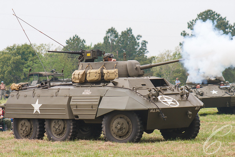 """Reenactors showcase World War II tanks, half-tracks and support vehicles during the Museum of the America G.I.'s annual Open House on March 29, 2008 in College Station, Texas. An American M8 """"Greyhound"""" armored car fires its 37mm gun for the assembled spectators."""