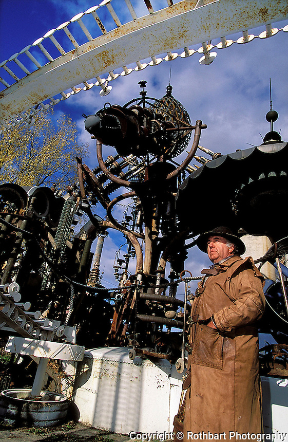 Artist Doc Evermor (also known as Tom Every) stands beneath his giant scrap metal sculpture, the Forevertron, in his Sauk Prairie, Wisconsin sculpture park.<br />  <br /> &copy; Michael Forster Rothbart<br /> www.mfrphoto.com <br /> 607-267-4893 o 607-432-5984<br /> 5 Draper St, Oneonta, NY 13820<br /> 86 Three Mile Pond Rd, Vassalboro, ME 04989<br /> info@mfrphoto.com<br /> Photo by: Michael Forster Rothbart<br /> Date: 10/01     File#:   color slide.