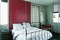 In the bedroom the large wrought-iron bed is contemporary but the red leather Carlo Mollino armchair dates from 1959