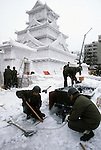 Japanese Self Defense Force snow sculptures turn snow into water that will be applied to help reinforce a snow sculpture in Odori Park. These are not traditional Frosty the Snowmen, but huge carved and chiseled Samurai Warriors, Buddhists gods, historical heroes of fairy tales and Walt Disney characters. Some stand as big as buildings. Chiseled out of tons of packed snow, the sculptures are the pride and job of the residents of Sapporo, Japan, who hosts the world famous Ice and Snow Sculpture Festival for five days in early February.Themes of the sculptures are picked from Kabuki stages, historical characters or fairy tales. (Jim Bryant Photo).