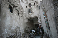 Monday 13 July, 2015: Residents are seen in a narrow street in the Old City of Sana'a, a 2,500-year-old cultural heritage site endangered after a fighter jet of the Saudi-led coalition bombed and destroyed a line of residential tower-houses killing 4 residents and reducing to rubble the historial site. The ongoing aerial campaign of bombardments by the Arab states and their western allies led by Saudi Arabia and the heavy fighting against the entrenchment of the Houthi insurgency along the Yemeni main cities from north to south has caused an international alert for the enlisted cultural heritage sites in Yemen, such as the historic town of Zabid, the Old City of Sana'a and the Old Walled City of Shibam. (Photo/Narciso Contreras)