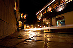 Cars drive through a small street in Cusco Peru at night