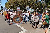 "Mohammed holds the ""Occupy Orange County"" sign as Occupy Orange County, Irvine marchers cross the intersection of Alton and Paseo Westpark in Irvine, CA as a part of their Saturday protest against banks.  Many signs are visible."