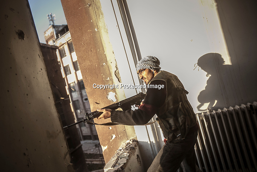 In this Tuesday, Oct. 30, 2012 photo, a rebel fighter belonging to the Liwa Al-Fatah aims on his enemy position from a school building during skirmishes with the Syrian army in the nearby Bustan Al-Pasha front line in Aleppo, Syrian's largest city. (AP Photo/Narciso Contreras).