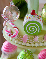Detail of baubles and other cake-themed Christmas decorations on an ornately iced tiered cake