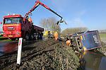 Foto: VidiPhoto<br /> <br /> BEESD - Een spectaculaire berging vrijdagmiddag van een vrachtwagen met oplegger bij het BP-tankstation langs de A2 bij Beesd. De vrachtwagencombinatie uit het Brabantse Asten was door de combinatie van sneeuw en gladheid van de weg bij de parkeerplaats gegleden. De chauffeur kwam met de schrik vrij. Takel- en Bergingsbedrijf Kooijman uit Vianen moest er met twee speciale takelwagens aan te pas komen om de truck weer uit de sloot te krijgen. Ook de bergingswagens hadden het vrijdag enorm druk door de vele ongevallen en glijpartijen. Ook de komende dagen worden door sneeuw en bevriezing van natte weggedeelten veel schademeldingen verwacht. De ochtendspits was door de winterse buien, sneeuwresten of bevriezing fors drukker dan normaal op een vrijdag. Door diverse ongevallen liep het verkeer op de A2 zowel in noordelijke als in zuidelijke richting compleet vast.