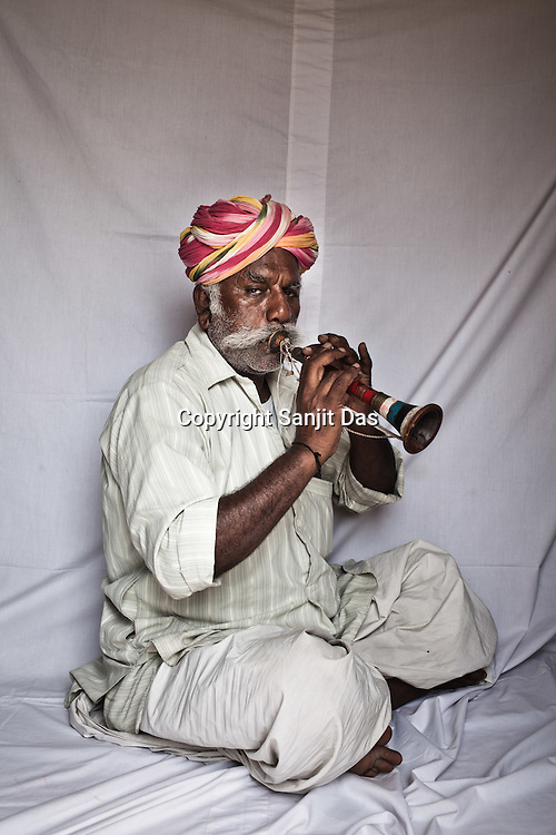 66-year-old Manganiyar artist and a Murli player, Pempa Khan poses for a portrait inside his house in Hamira village of Jaiselmer district in Rajasthan, India. Photo: Sanjit Das/Panos