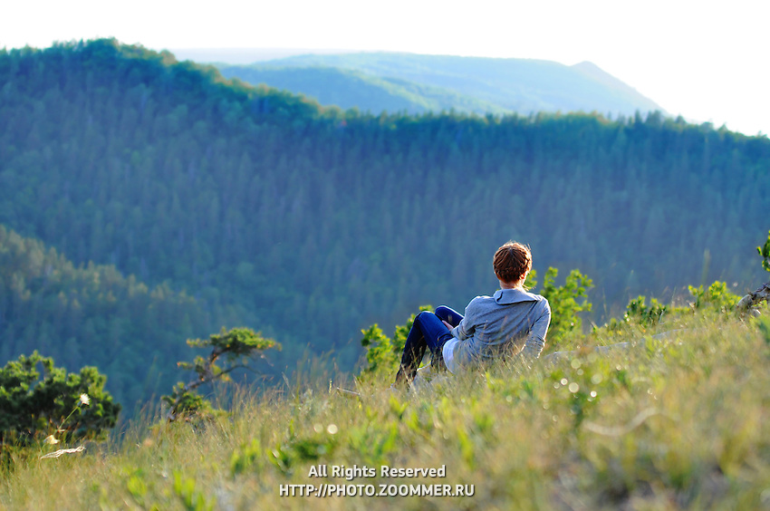 Girl on a steep hill sitting on the grass looks over the Zhiguli mountains covered with trees