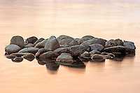 Just a bunch of pebbles in the almost still waters of the Po River at sunset.