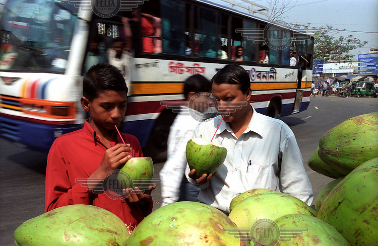 Two thirsty city dwellers drink the water of green coconuts from a roadside stall.