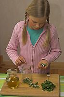 Mädchen macht Heilöl mit Gänseblümchen und Olivenöl, zerkleinerte Gänseblümchen werden in ein Glas gefüllt, Bellis perennis, Daisy
