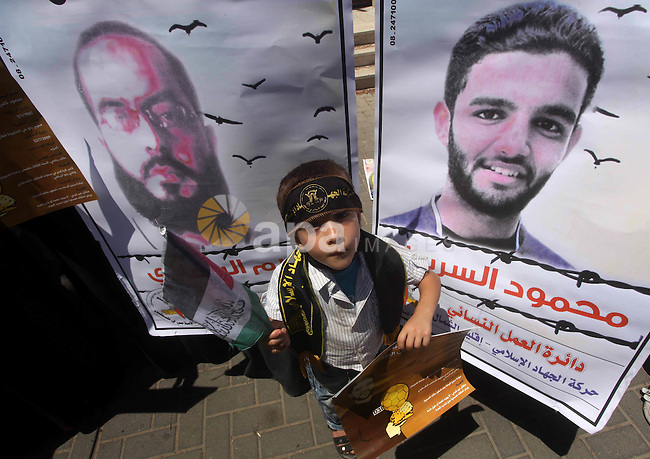 A Palestinian child holds pictures of Palestinian prisoners Mahmoud Al-Sarsak and Akram Al-Rikhawi, whose are still refusing food for 86 days after a deal was made to end a mass prisoner hunger strike, during a demonstration in their support, in front of the UNRWA headquarters in the Gaza city on 12 June, 2012. Photo by Ashraf Amra