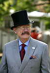 A man in a top hat looks around at the horses  before a four in hand coaching event in Locust, New Jersey.