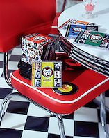 A set of CD's sit atop a chair in a 1950's diner vignette